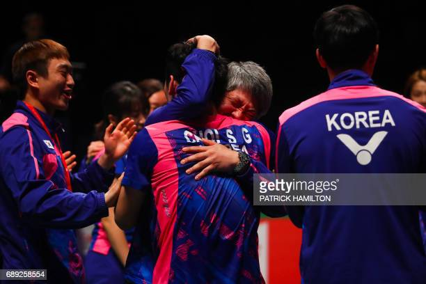 South Korea's head coach Kang KyungJin embraces player Choi SolGyu following the team's victory over China in the team final at the 2017 Sudirman Cup...