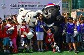South Korea's honorary ambassador and 2010 Olympic figure skating champion Kim YuNa with students alongside the mascots for the 2018 Pyeongchang...