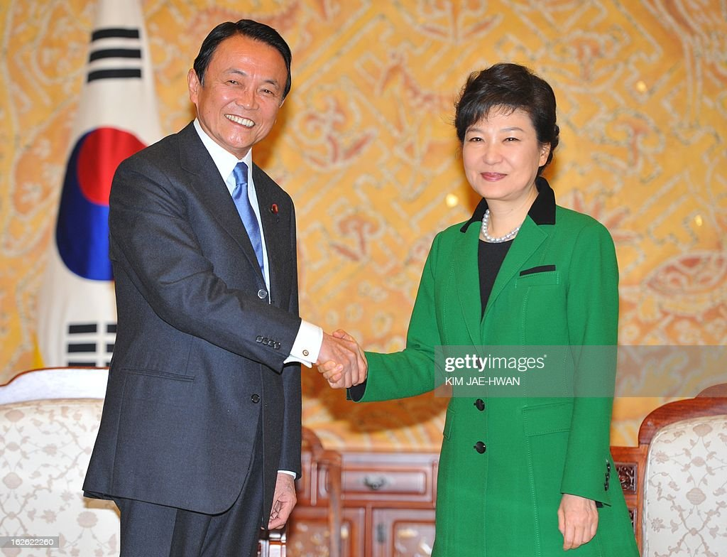 South Korea's incoming president Park Geun-Hye (R) shakes hands with Japan's deputy prime minister Taro Aso at the presidential Blue House in Seoul on February 25, 2013. Park Geun-Hye became South Korea's first female president on February 25, vowing zero tolerance with North Korean provocation and demanding Pyongyang 'abandon its nuclear ambitions' immediately. AFP PHOTO / POOL / KIM JAE-HWAN