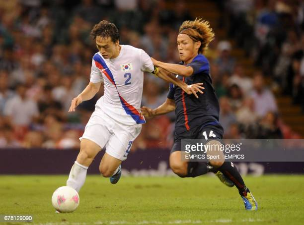 South Korea's Jaesuk Oh and Japan's Takashi Usami battle for the ball during the men's football Bronze medal match at the Millennium Stadium