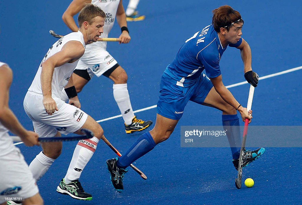 South Korea's Kang Moon Kweon dribbles past New Zealand's Dean Couzins during a third place playoff match at the Sultan Azlan Shah Cup men's field...