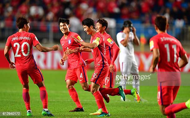 South Korea's Ki SungYueng celebrates his goal with teammates against Qatar during their 2018 World Cup qualifying football match in Suwon south of...