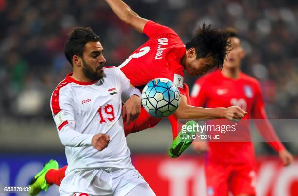 South Korea's Kim JinSu vies for the ball with Syria's Mrdkian Mardek during their World Cup football qualifying match in Seoul on March 28 2017 /...