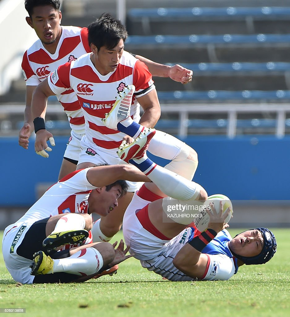South Korea's Kim Sung Soo (R) falls on the ground following a tackle by Japanese players during the Asian Rugby Championship rugby match in Yokohama on April 30, 2016. / AFP / KAZUHIRO