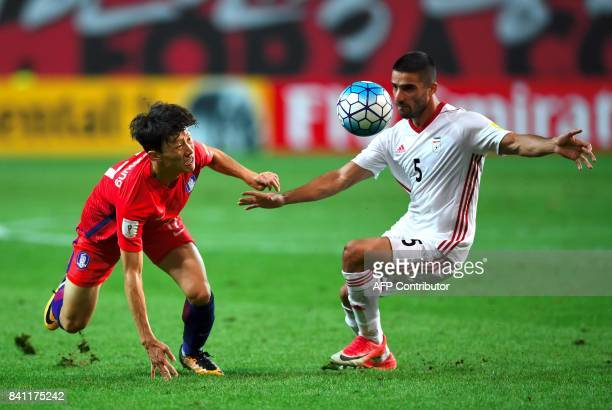South Korea's Lee JaeSung fights for the ball with Iran's Milad Mohammadi during the FIFA 2018 World Cup qualifying football match in Seoul on August...