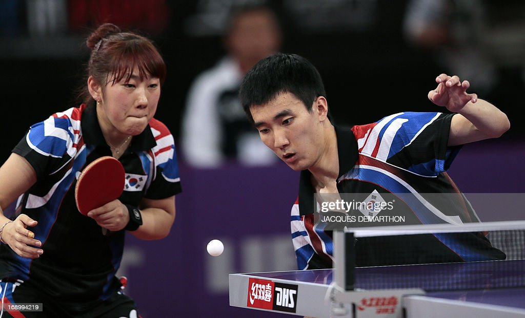 South Korea's Lee Sangsu (R) and Park Youngsook (L) compete against North Korea's Kim Hyok Bong and Kim Jong in the final match of the mixed doubles of the World Table Tennis Championships on May 18, 2013 in Paris. North Korea won the title. AFP PHOTO / Jacques DEMARTHON
