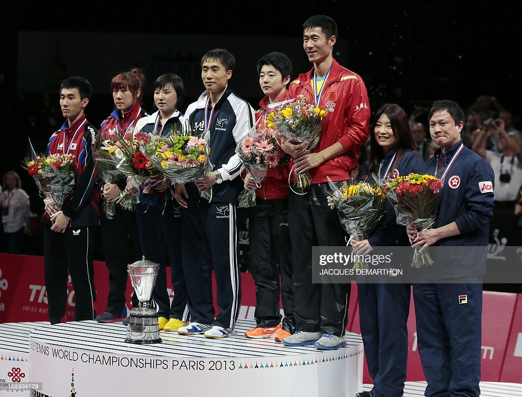 South Korea's Lee Sangsu (L) and Park Youngsook (2nd L), North Korea's Kim Jong (3rd L) and Kim Hyok Bong (4th L), China's Rao Jingwen (4th R) and Wang Liqin (3rd R), and Hong Kong's Jiang Huajun (2nd R) and Cheung Yuk (R) stand on the podium of the mixed doubles category of the World Table Tennis Championships on May 18, 2013 in Paris. North Korea won the title. AFP PHOTO / Jacques DEMARTHON