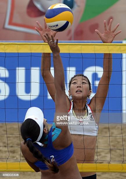 South Korea's Lee Una tries to block a shot by Thailand's Usa Tenpaksee during the womens beach volleyball preliminary round match of the 2014 Asian...