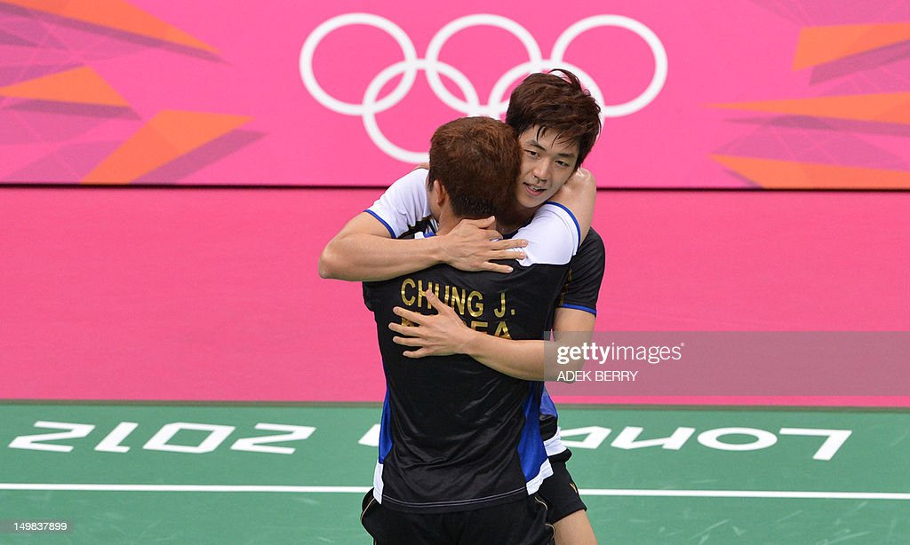 South Korea's Lee Yong Dae and Chung Jae Sung (foreground) celebrate their victory over Koo Kien Keat and Tan Boon Heong of Malaysia during the bronze medal men's doubles badminton match at the London 2012 Olympic Games in London on August 5, 2012. South Korean won the match 23-12, 21-10. AFP PHOTO /ADEK BERRY
