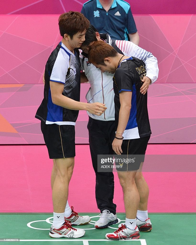 South Korea's Lee Yong Dae (L) and Chung Jae Sung (R) hug their coach after beating Koo Kien Keat and Tan Boon Heong of Malaysia during the bronze medal men's doubles badminton match at The London 2012 Olympic Games in London on August 5, 2012. South Korea won the match 23-12, 21-10.