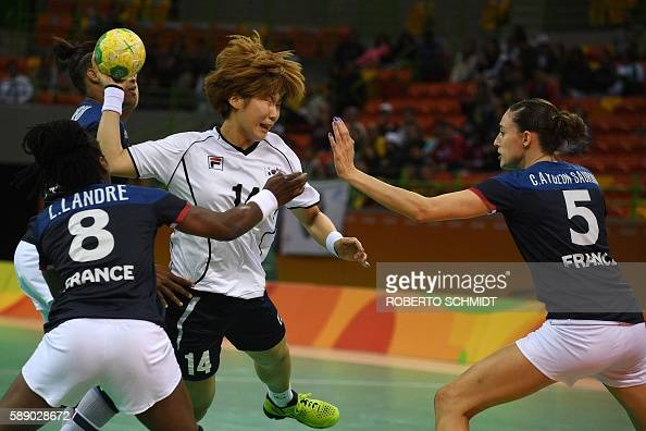 TOPSHOT South Korea's left back Kim Jinyi vies with France's pivot Laurisa Landre and France's right back Camille Ayglon Saurina during the women's...