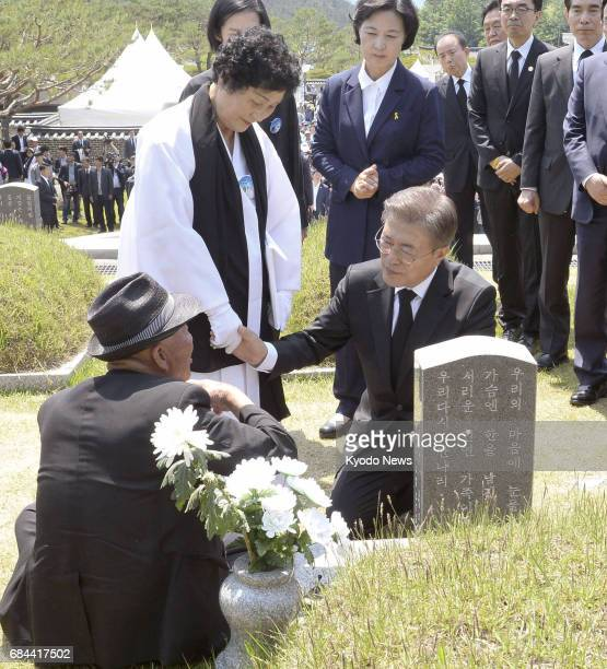South Korea's new President Moon Jae In talks to people who lost their relatives at a 1980 prodemocracy uprising during a ceremony marking the 37th...
