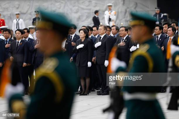 South Korea's new President Moon JaeIn and his wife Kim JungSuk salute to the national flag at the National Cemetery on May 10 2017 in Seoul South...