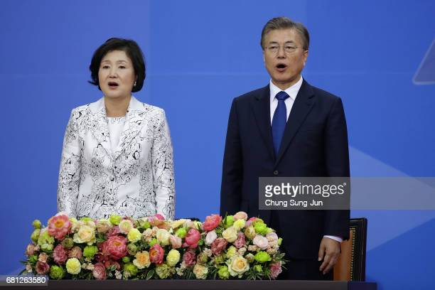 South Korea's new President Moon JaeIn and his wife Kim JungSuk sing the national anthem during the presidential inauguration ceremony at National...