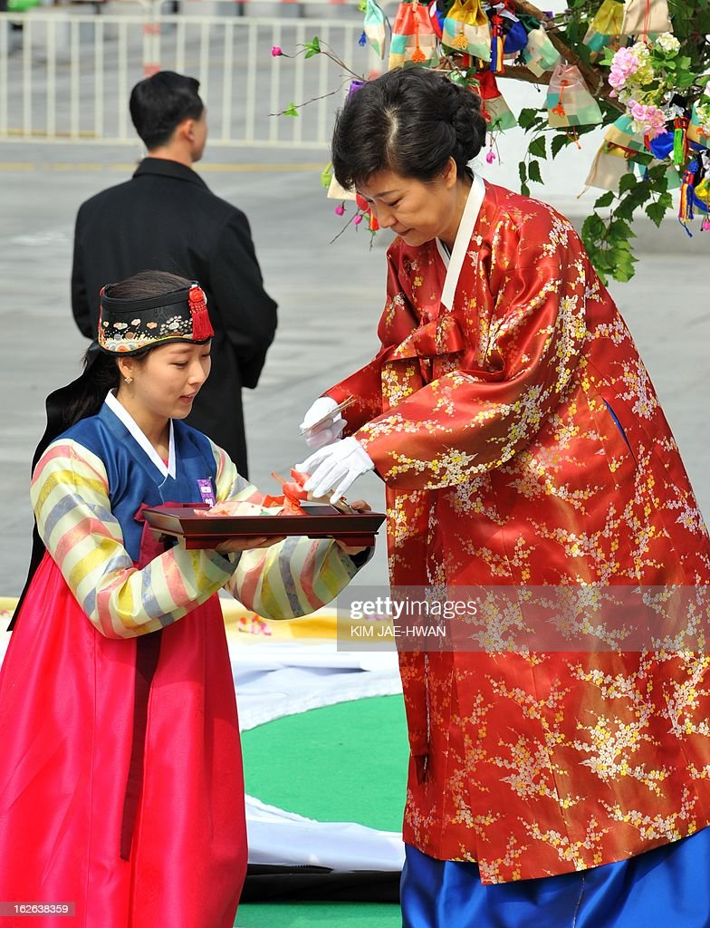 South Korea's new President Park Geun-Hye (R) wearing a traditional Hanbok dress opens a hope letter from citizens at a plaza on her way to the presidential Blue House after her inauguration in Seoul February 25, 2013. Park Geun-Hye was sworn in as South Korea's first female president on February 25, vowing zero tolerance with provocations from a nuclearised North Korea and a new era of economic prosperity for all. AFP PHOTO / KIM JAE-HWAN