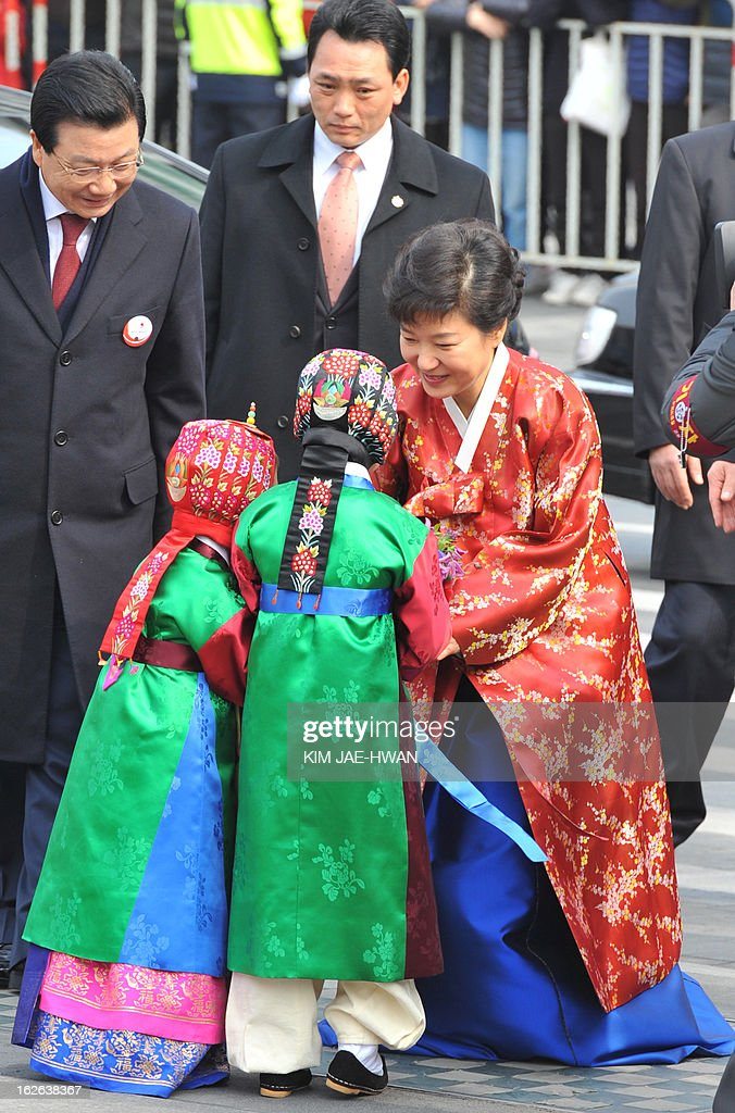 South Korea's new President Park Geun-Hye (R) wearing a traditional Hanbok dress is greeted by children at a plaza on her way to the presidential Blue House after her inauguration in Seoul February 25, 2013. Park Geun-Hye was sworn in as South Korea's first female president on February 25, vowing zero tolerance with provocations from a nuclearised North Korea and a new era of economic prosperity for all. AFP PHOTO / KIM JAE-HWAN