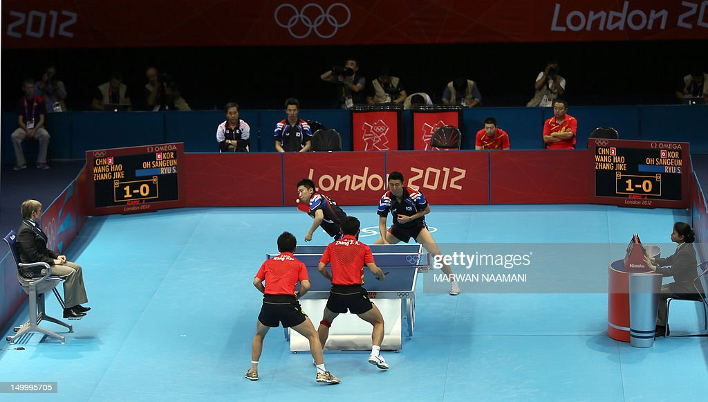 South Korea's Oh Sangeun and South Korea's Ryu Seungmin (back) return a ball to China's Wang Hao and Zhang Jike during the table tennis men's team final China vs South Korea at the London Olympic games on August 8, 2012 at the Excel arena in London.