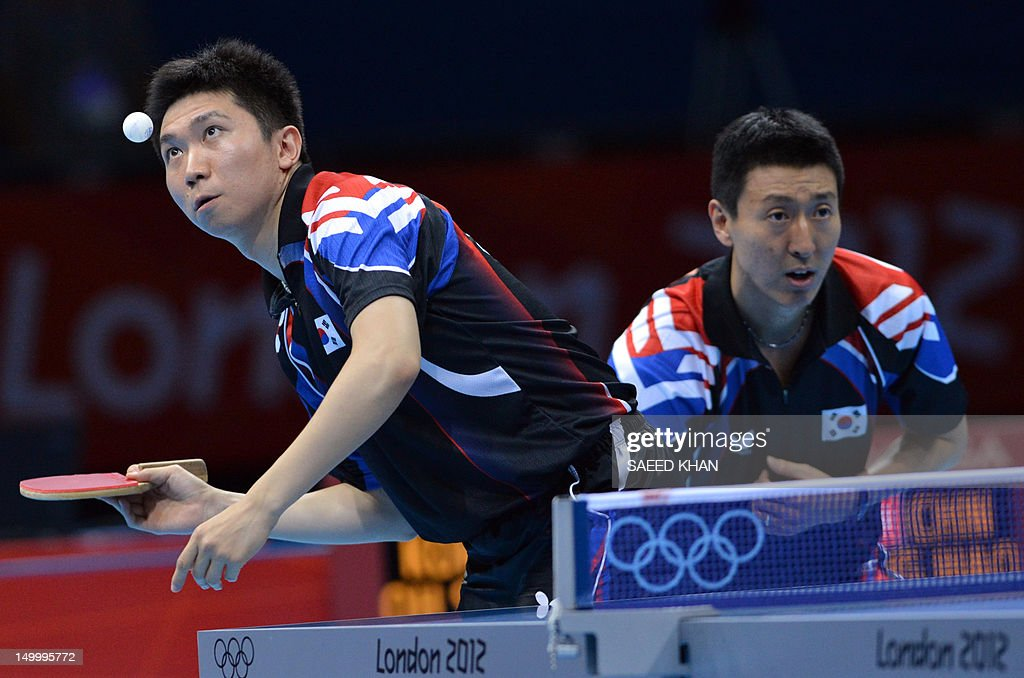 South Korea's Oh Sangeun and South Korea's Ryu Seungmin (front) return a ball to China's Wang Hao and Zhang Jike during the table tennis men's team final China vs South Korea at the London Olympic games on August 8, 2012 at the Excel arena in London.