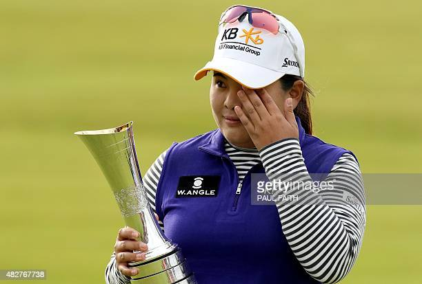 South Korea's Park Inbee wipes away a tear as she celebrates her victory with the trophy after her final round 65 on day four of the Women's British...
