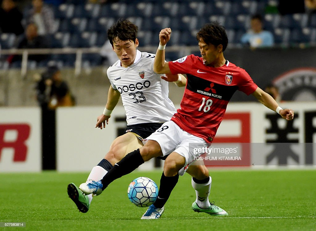 South Korea's Pohang Steelers defender Lee Namgyu (L) fights for the ball with Japan's Urawa Reds midfielder Yoshiaki Komai (R) during their AFC champions league group H football match in Saitama on May 3, 2016. / AFP / TOSHIFUMI