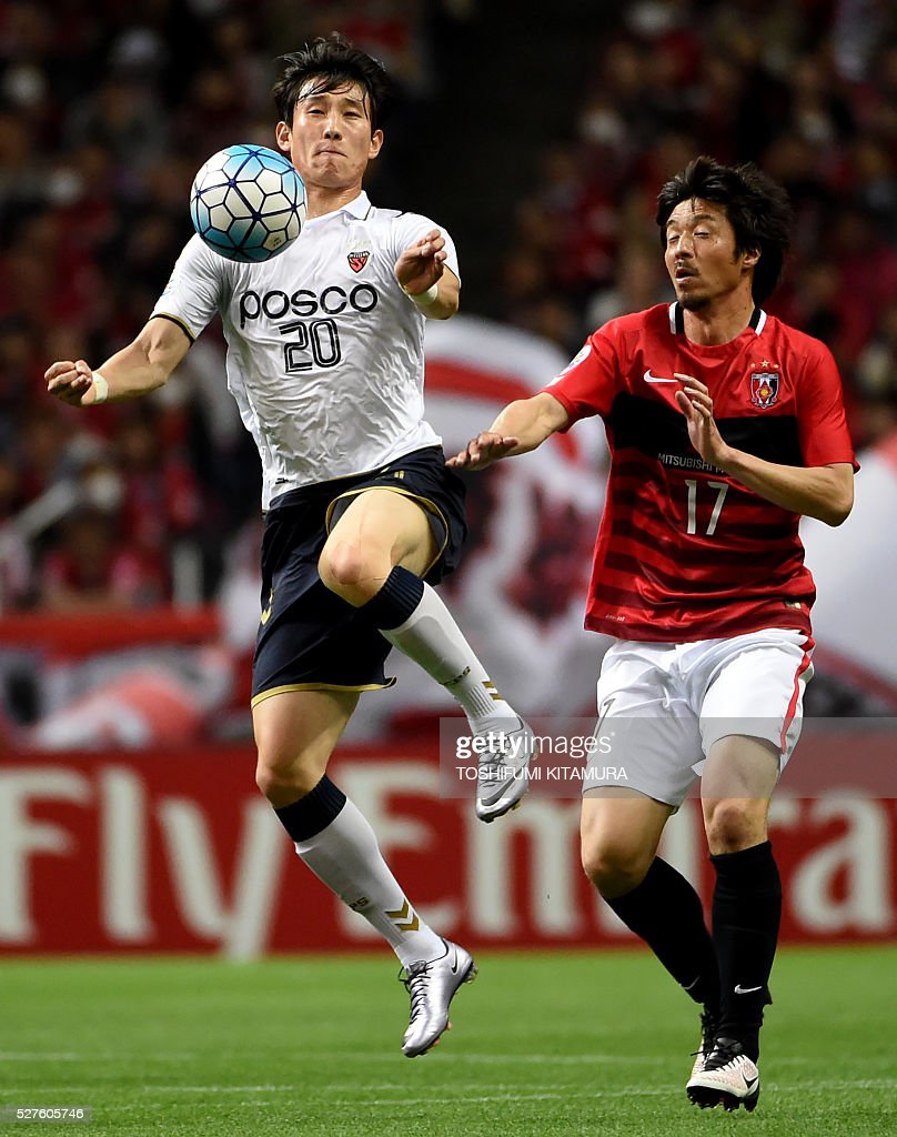 South Korea's Pohang Steelers forward Choe Hoju (L) fights for ball with Japan's Urawa Reds defender Mitsuru Nagata (R)during their AFC champions league group H football match in Saitama on May 3, 2016. / AFP / TOSHIFUMI