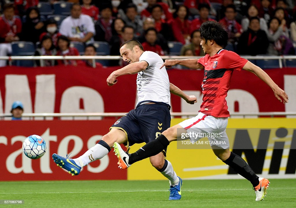 South Korea's Pohang Steelers forward Veselinovic Lazar (L) shoots beside Japan's Urawa Reds defender Daisuke Nasu (R) during their AFC champions league group H football match in Saitama on May 3, 2016. / AFP / TOSHIFUMI