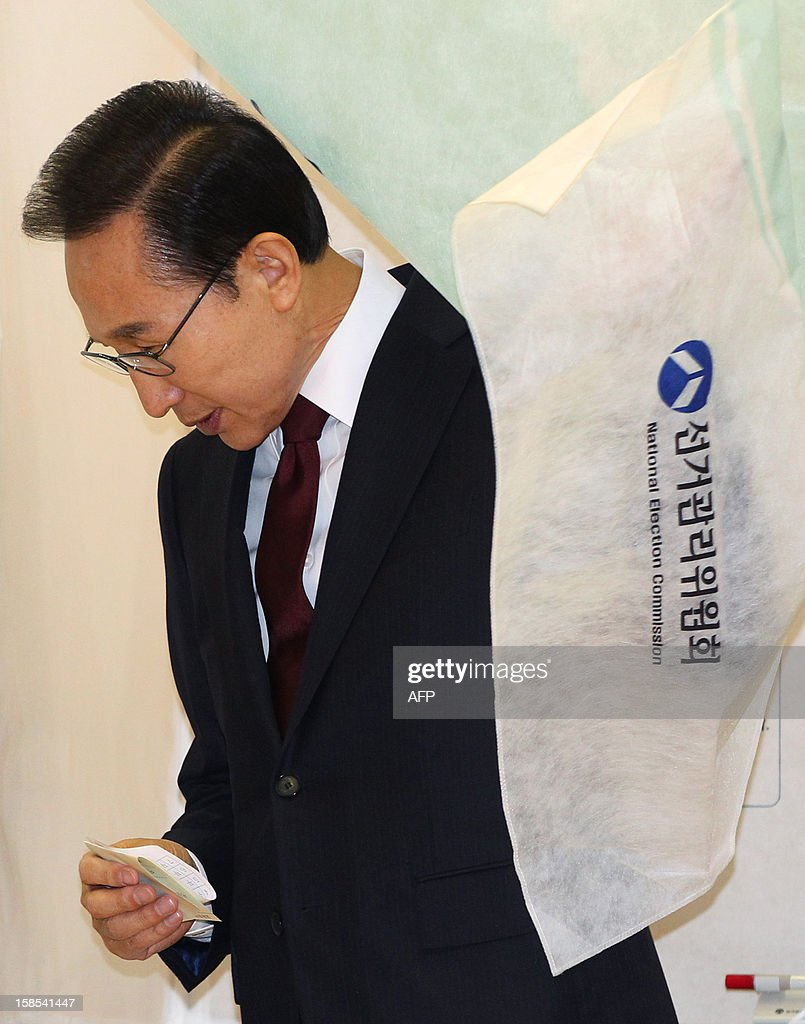 South Korea's President Lee Myung-Bak exits the voting booth to cast his ballot in South Korea's presidential election at a polling station in Seoul on December 19, 2012. South Koreans went to the polls to choose a new president in a close and potentially historic election that could result in Asia's fourth-largest economy getting its first female leader. AFP PHOTO / POOL / Ahn Young-joon