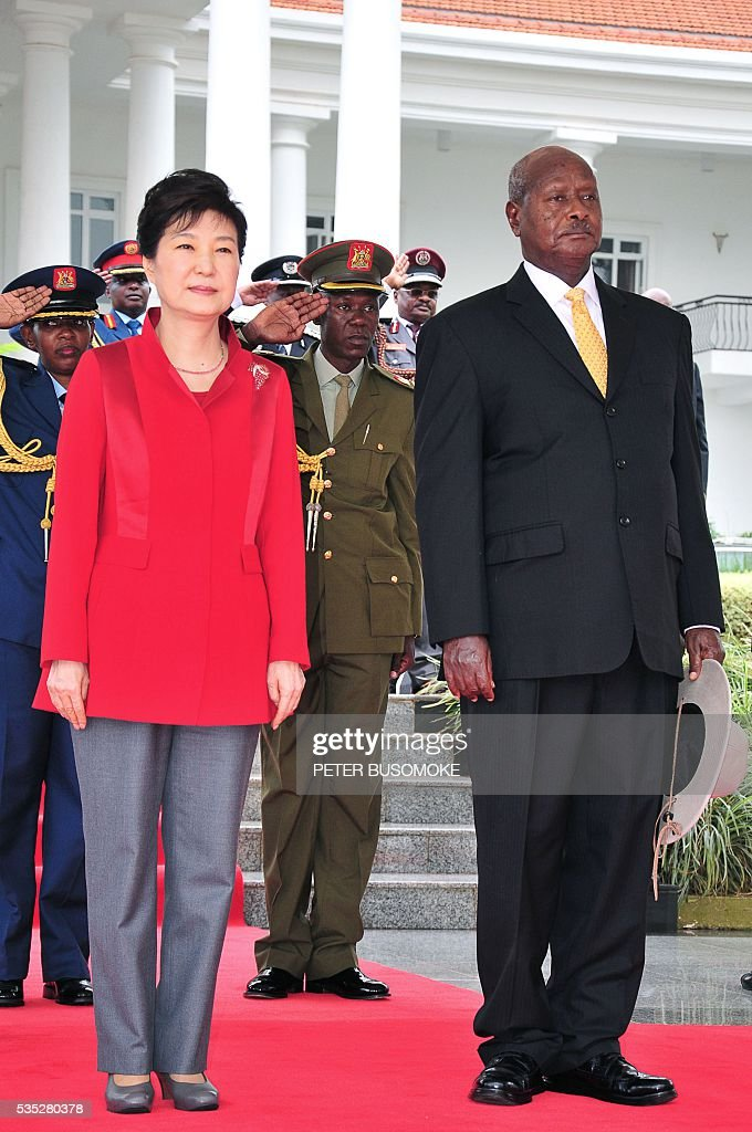 South Korea's President Park Geun-hye (L) and Uganda's President Yoweri Museveni (R) listen to a 21-gun salute after inspecting of a guard of honour of the Uganda People's Defence Force (UPDF), at State House in Entebbe, on May 29, 2016. Museveni vowed to cut military and security ties with North Korea in line with UN sanctions imposed following Pyongyang's nuclear and missile tests, a Seoul official said on May 29. / AFP / Peter BUSOMOKE