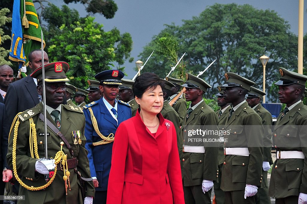 South Korea's President Park Geun-Hye (C) inspects of a guard of honour of the Uganda People's Defence Force (UPDF), at State House in Entebbe, on May 29, 2016. Museveni vowed to cut military and security ties with North Korea in line with UN sanctions imposed following Pyongyang's nuclear and missile tests, a Seoul official said on May 29. / AFP / Peter BUSOMOKE
