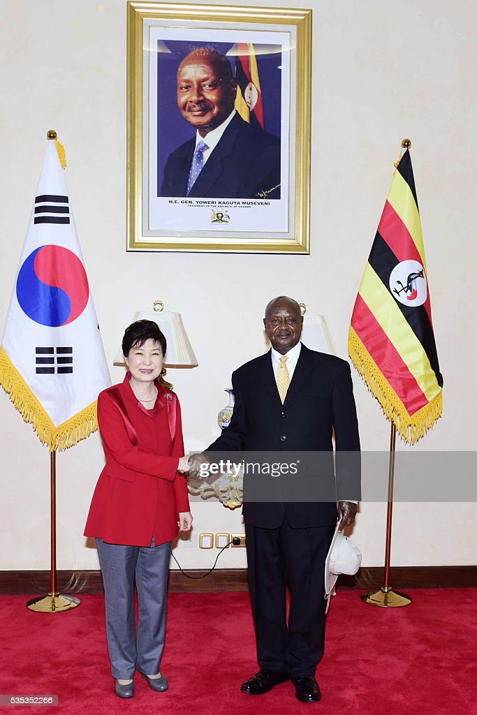 South Korea's President Park Geun-Hye (R) shakes hands with Uganda's President Yoweri Museveni (R) during a meeting at State House in Entebbe, on May 29, 2016. Museveni vowed to cut military and security ties with North Korea in line with UN sanctions imposed following Pyongyang's nuclear and missile tests, a Seoul official said on May 29. / AFP / -