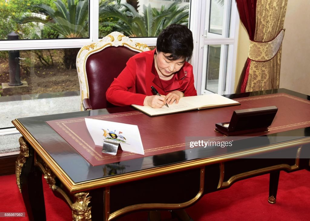 South Korea's President Park Geun-Hye (L) signs a book after a meeting with Uganda's President at State House in Entebbe, on May 29, 2016. Museveni vowed to cut military and security ties with North Korea in line with UN sanctions imposed following Pyongyang's nuclear and missile tests, a Seoul official said on May 29. / AFP / -
