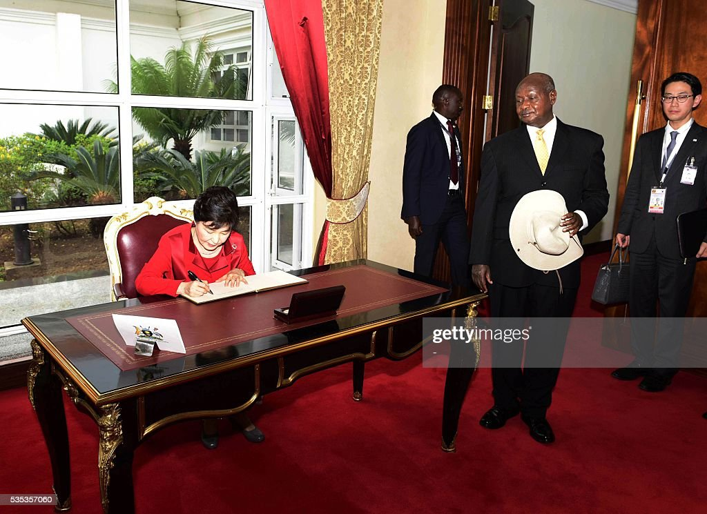 South Korea's President Park Geun-Hye (L) signs a book as Uganda's President Yoweri Museveni (L) looks on at State House in Entebbe, on May 29, 2016. Museveni vowed to cut military and security ties with North Korea in line with UN sanctions imposed following Pyongyang's nuclear and missile tests, a Seoul official said on May 29. / AFP / -