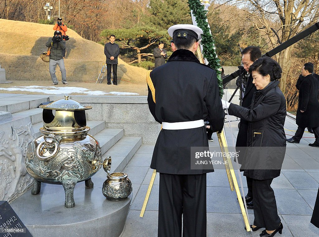 South Korea's president-elect, Park Geun-Hye (R) of ruling New Frontier Party, offers a wreath as she visits the grave of her father Park Chung-Hee, the country's former dictator, at the National Cemetery in Seoul on December 20, 2012 the day after she won the country's presidential election. South Korea elected its first woman president on December 19, with voters handing the slim but historic victory to conservative candidate Park Geun-Hye, daughter of the country's former military ruler. AFP PHOTO / POOL / JUNG YEON-JE