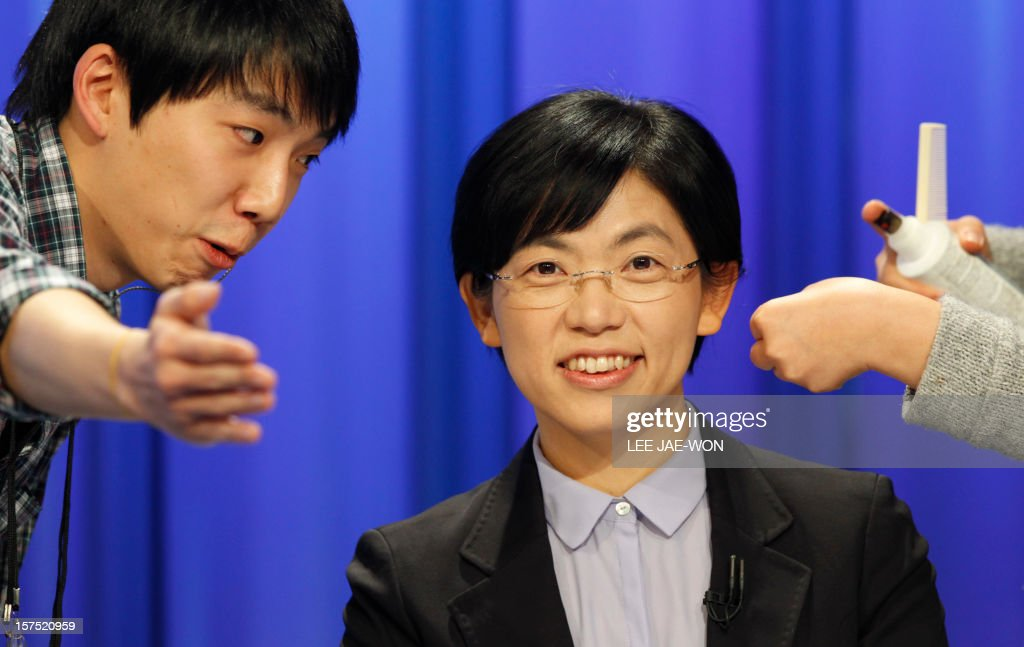 South Korea's presidential candidate Lee Jung-Hee (C) of the opposition Unified Progressive Party talks with a staff member of a TV station before a televised debate in Seoul on December 4, 2012. Conservative and right wing Park who is the daughter of late South Korean military dictator Park Chung-hee and the former human rights lawyer Moon, participated in a debate over security policy as North Korea readied a rocket launch that is timed to coincide with the South's presidential election.