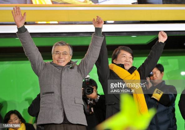 South Korea's presidential candidate Moon JaeIn of opposition Democratic United Party poses with software mogul Ahn CheolSoo who had run as an...