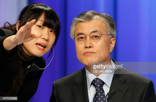 South Korea's presidential candidate Moon JaeIn of the main opposition Democratic United Party talks with a staff member of a TV station before a...