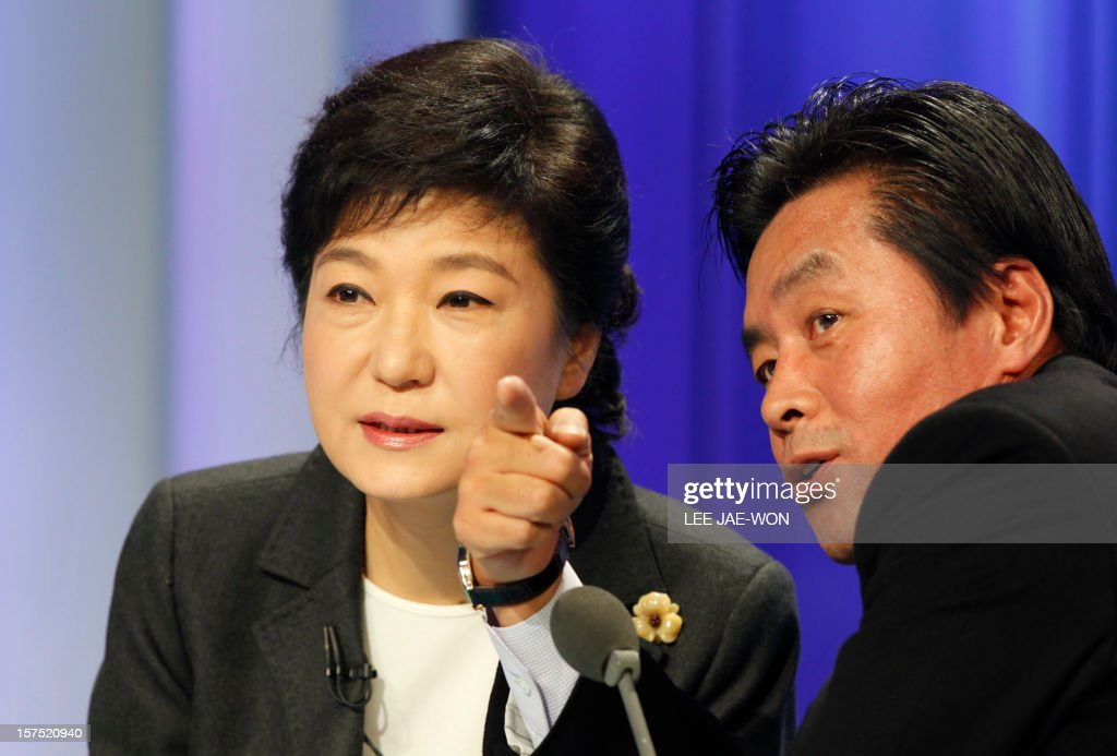 South Korea's presidential candidate Park Geun-Hye (L) of the ruling Saenuri Party talks with her aide before a televised debate in Seoul on December 4, 2012. Conservative and right wing Park who is the daughter of late South Korean military dictator Park Chung-hee and the former human rights lawyer Moon, participated in a debate over security policy as North Korea readied a rocket launch that is timed to coincide with the South's presidential election. AFP PHOTO / POOL
