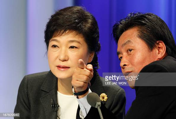 South Korea's presidential candidate Park GeunHye of the ruling Saenuri Party talks with her aide before a televised debate in Seoul on December 4...