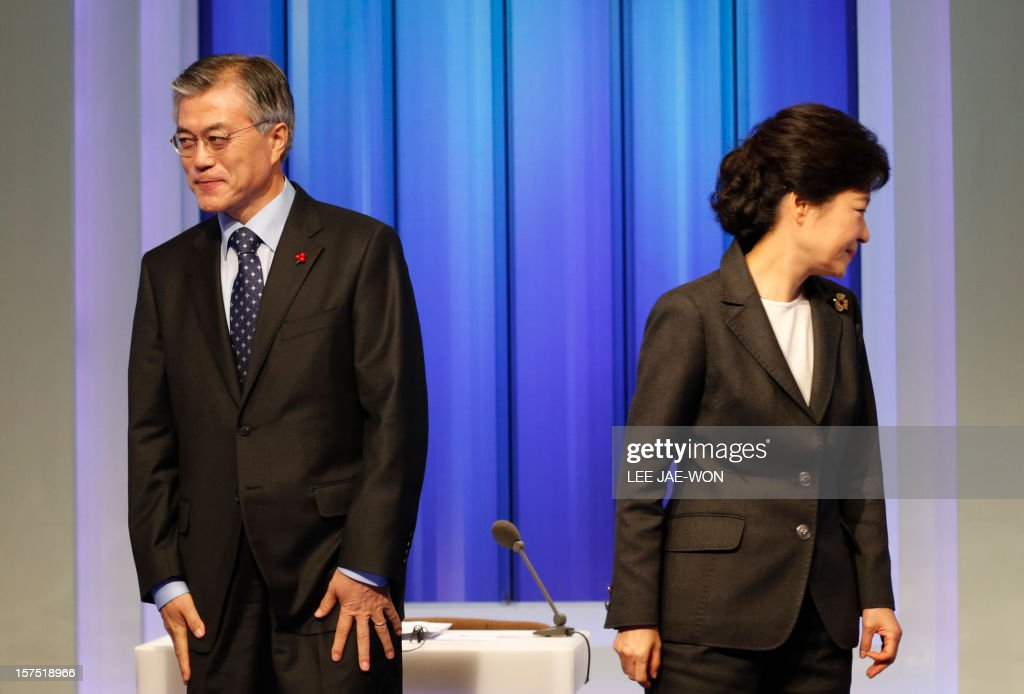 South Korea's presidential candidates Moon Jae-In (L) of the main opposition Democratic United Party and Park Geun-Hye of THE ruling Saenuri Party return to their seats after posing before a televised debate in Seoul on December 4, 2012. Conservative and right wing Park who is the daughter of late South Korean military dictator Park Chung-hee and the former human rights lawyer Moon, participated in a debate over security policy as North Korea readied a rocket launch that is timed to coincide with the South's presidential election. AFP PHOTO / POOL