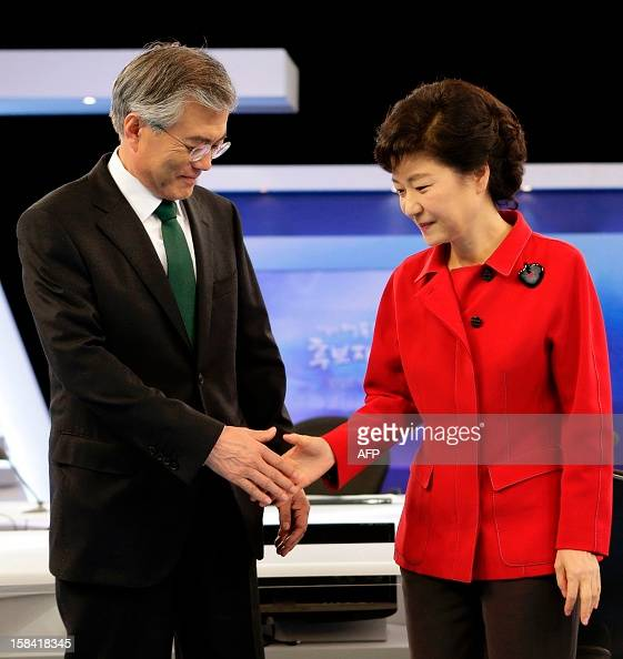 South Korea's presidential candidates Park Geunhye of ruling Saenuri Party shakes hands with Moon Jaein of Democratic United Party before a final...