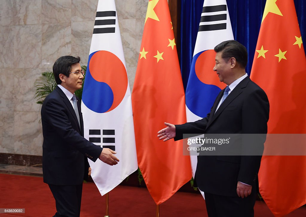 South Korea's Prime Minister Hwang Kyo-ahn (L) is greeted by Chinese President Xi Jinping (R) before a meeting at the Great Hall of the People in Beijing on June 29, 2016. / AFP / POOL / GREG