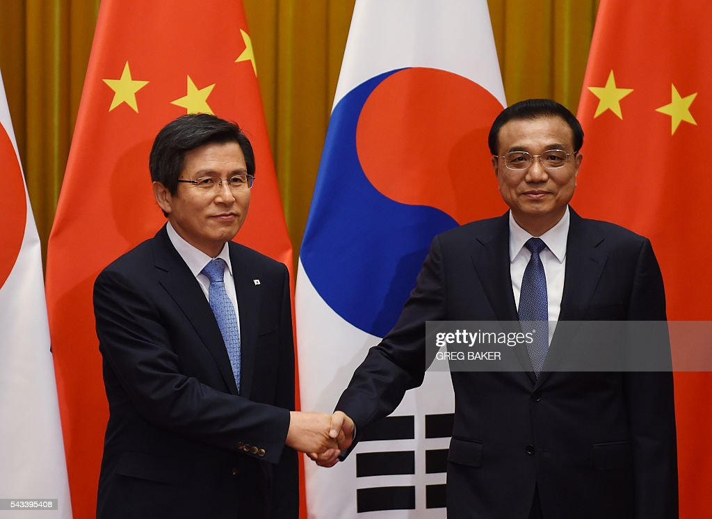 South Korea's Prime Minister Hwang Kyo-ahn (L) shakes hands with Chinese Premier Li Keqiang ahead of their meeting at the Great Hall of the People in Beijing on June 28, 2016. / AFP / POOL / GREG