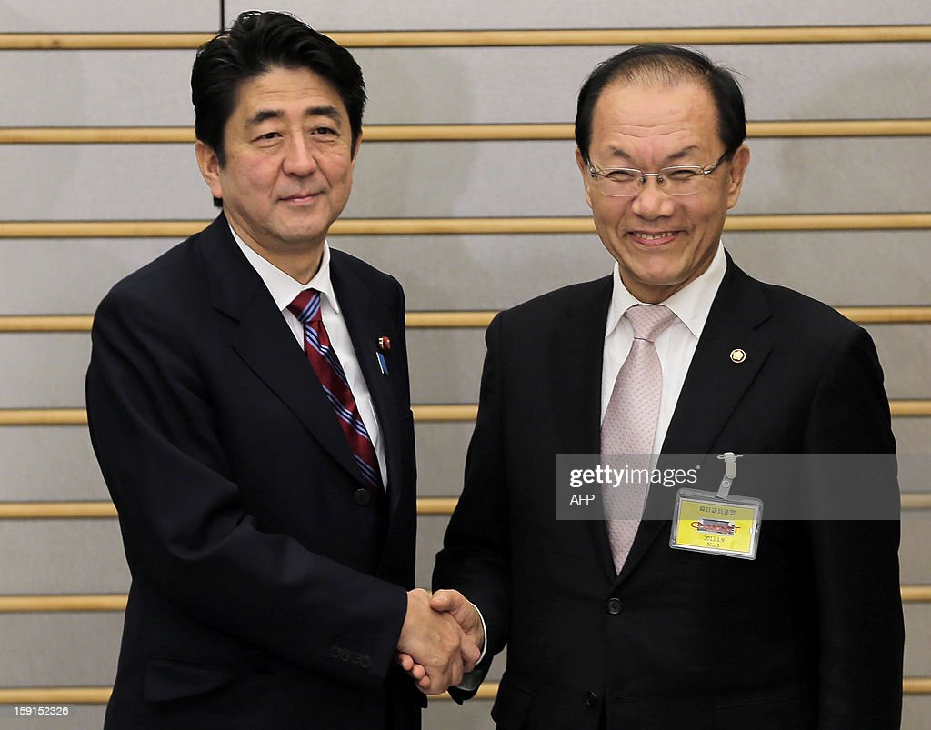 South Korea's ruling party Saenuri chairman Hwang Woo-yea, (R) is greeted by Japanese Prime Minister Shinzo Abe prior to their meeting at the prime minister's official residence in Tokyo on January 9, 2013. The meeting between the two Asian neighbours took place only weeks after Abe returned as Japan's prime minister. AFP PHOTO / Itsuo Inouye / POOL