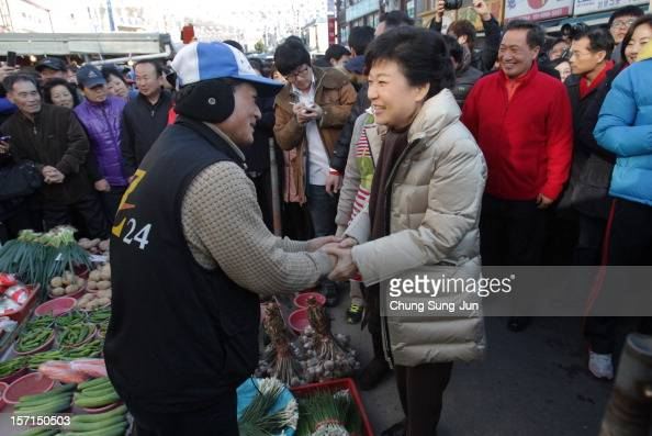 South Korea's ruling Saenuri Party's presidential candidate Park GeunHye greets a stallholder as she takes to downtown streets to begin her...