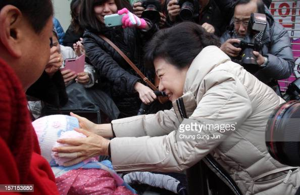 South Korea's ruling Saenuri Party's presidential candidate Park GeunHye greets a child as she takes to downtown streets to begin her presidential...
