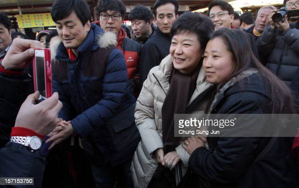 South Korea's ruling Saenuri Party's presidential candidate Park GeunHye poses with supporters as she takes to downtown streets to begin her...
