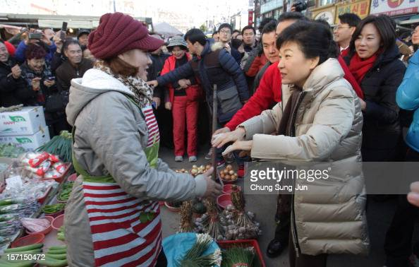 South Korea's ruling Saenuri Party's presidential candidate Park GeunHye speaks with a stall holder as she takes to the downtown streets to begin her...