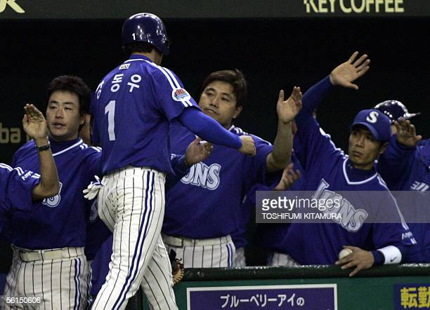 South Korea's Samsung Lions outfielder Kang DongWoo is welcomed by his team mates after scoring in the third innings of the final game of the Asia...