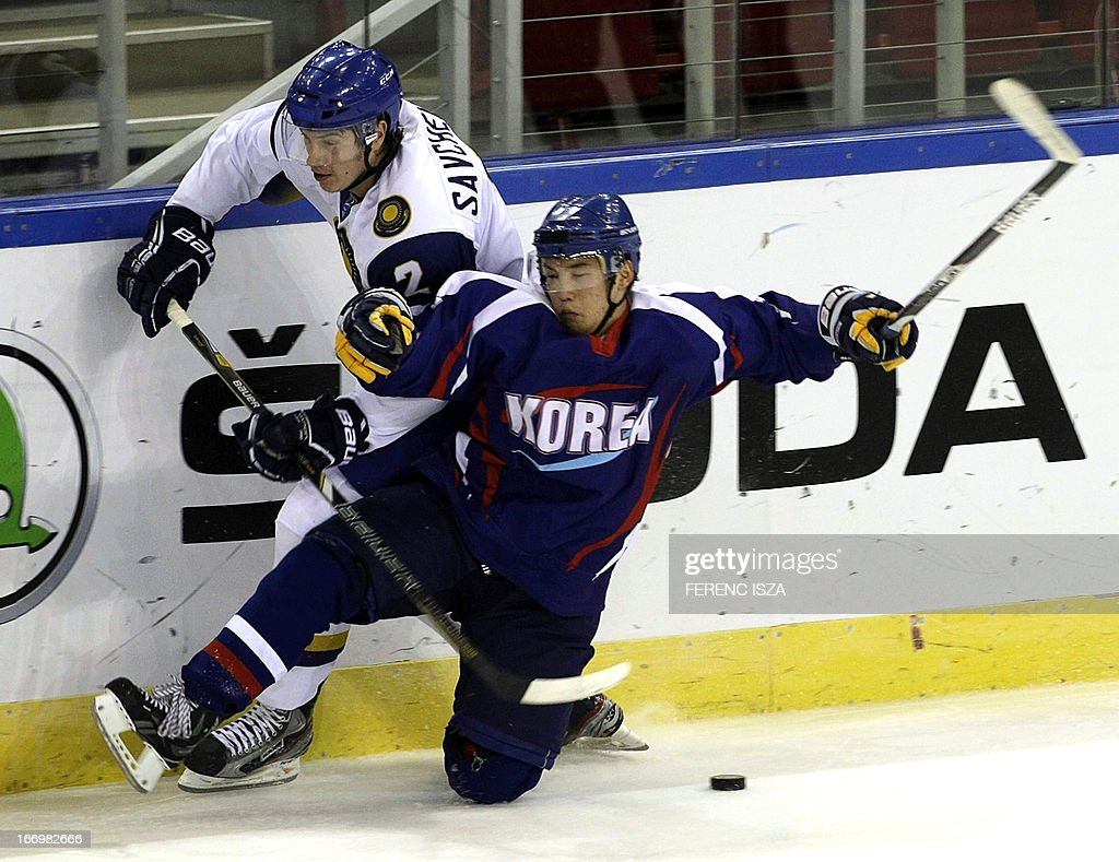South Korea's Sanghoon Shin (R) fights for the puck with Kazakhstan's defender Roman Savchenko (R) on April 19, 2013 at the Budapest Sport Arena during their IIHF Ice Hockey World Championship Division 1 Group A match. ISZA