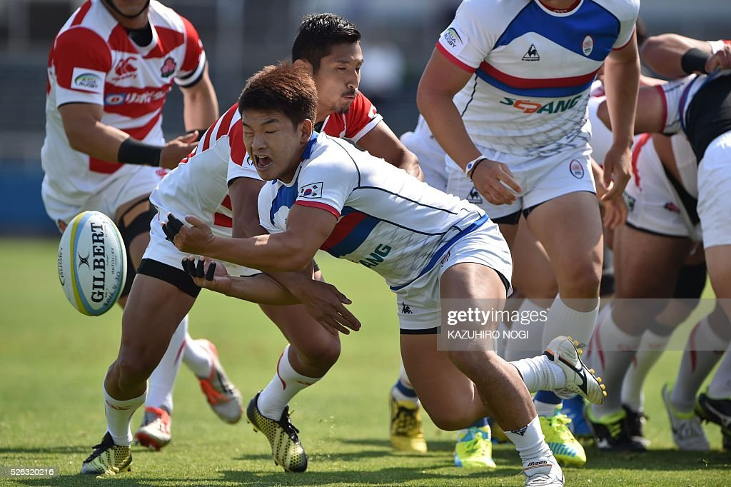 South Korea's scrum-half Shin Ki Cheol (C) is tackled by Japan's scrum-half Keisuke Uchida (C, rear) during the Asian Rugby Championship rugby match in Yokohama on April 30, 2016. / AFP / KAZUHIRO